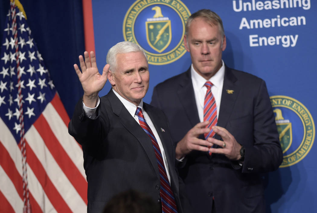 In this June 29, 2017, file photo, Vice President Mike Pence, left, waves as he is introduced to speak at the Department of Energy in Washington, as Interior Secretary Ryan Zinke watches. As forme ...