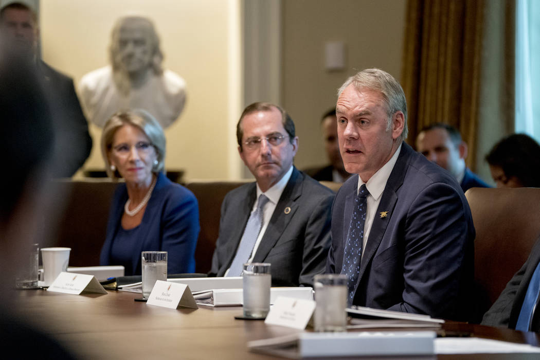 In this Thursday, Aug. 16, 2018 file photo, Interior Secretary Ryan Zinke, right, accompanied by Education Secretary Betsy DeVos, left, and Health and Human Services Secretary Alex Azar, center, s ...