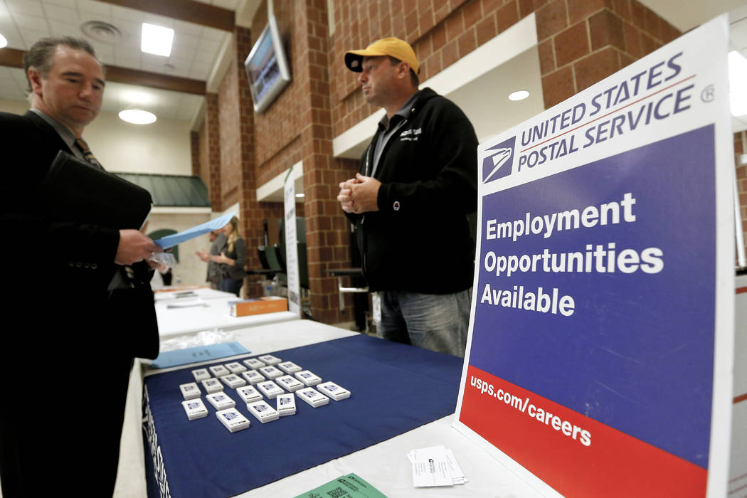 A recruiter from the postal service, right, speaks with an attendee of a job fair in the cafeteria of Deer Lakes High School in Cheswick, Pa. (Keith Srakocic/AP, File)