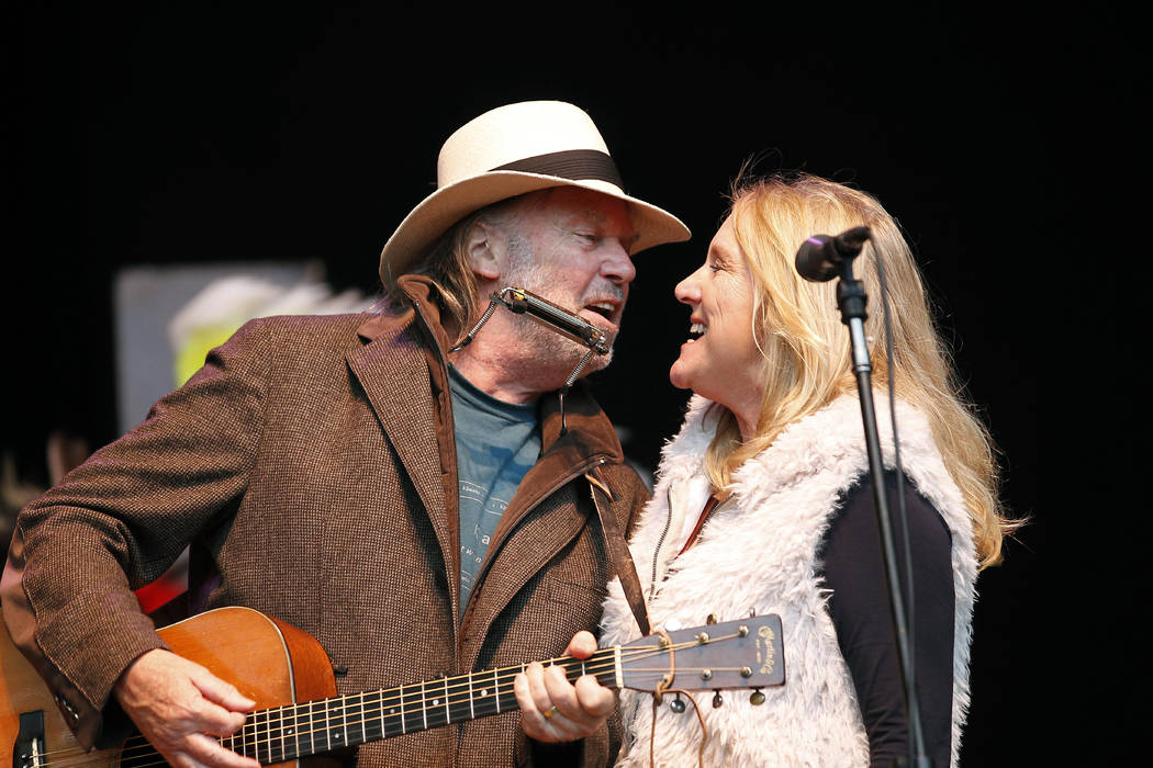 Neil Young, left, and his wife Pegi Young perform during the Bridge School Benefit concert in Mountain View, Calif. on Oct. 24, 2010. (AP Photo/Tony Avelar, File)