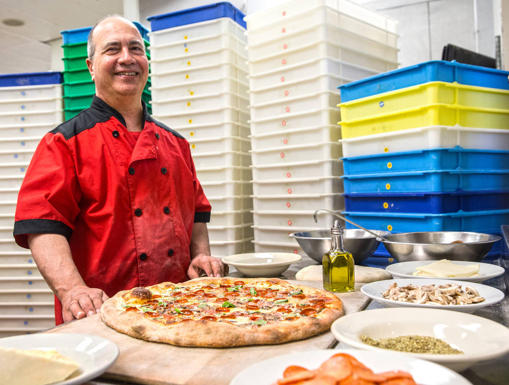 Chef/co-owner John Arena adds fresh basil to an Olde New York specialty pizza, with dozens of treys of pizza dough prepared in advance for the Super Bowl LI rush covering the wall behind him, on T ...