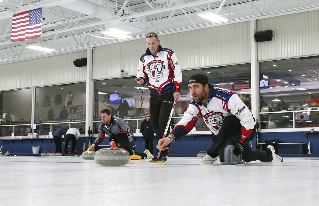 In this Jan. 3, 2019 photo, former Minnesota Vikings football player Jared Allen, right, practices with his curling team for a competition as coach and former Olympian John Benton watches in Blain ...