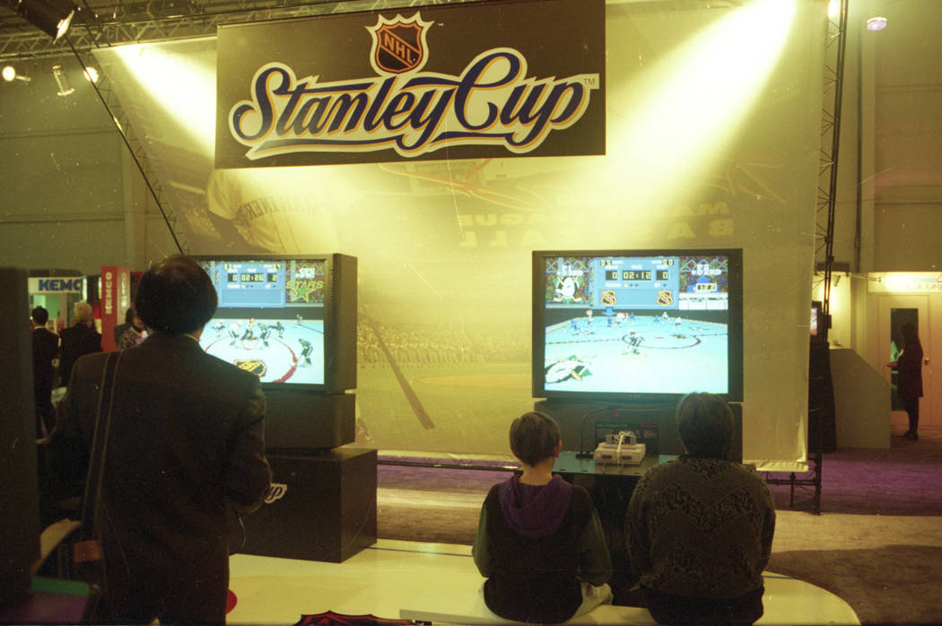 Two people play the NHL Stanley Cup game on the Super Nintendo gaming system on a big screen television at the 1993 Consumer Electronics Show at the Las Vegas Convention Center.