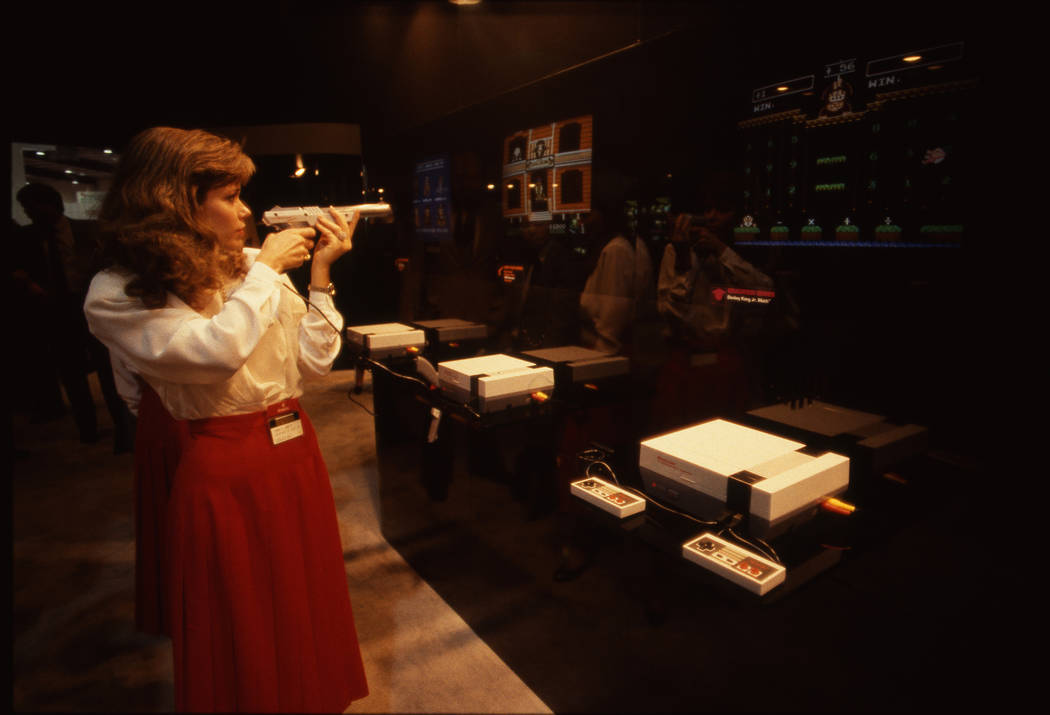 A woman plays a video game on an NES console at the 1987 CES show at the Las Vegas Convention Center. (Jim Laurie/Las Vegas Review-Journal)