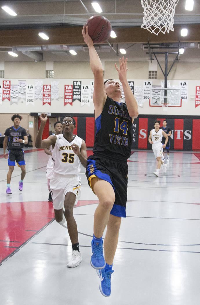 Sierra Vista junior Valton Mesic (14) converts a fast break layup past Bonanza senior Ian White (35) in the first quarter during the semifinals of the Vegas Invitational boys basketball tournament ...