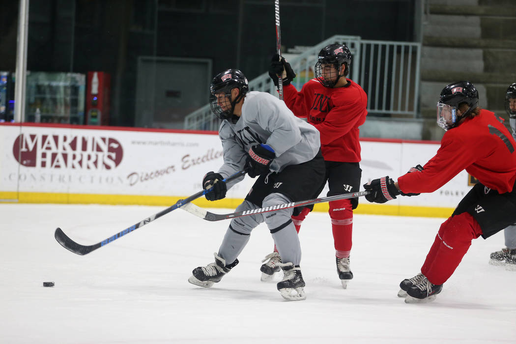 Jared Turcotte, from left, looks for a shot under pressure from Jordan Rea, and Tommy Harrison during an UNLV hockey team practice at City National Arena in Las Vegas, Friday, Jan. 4, 2019. Erik V ...