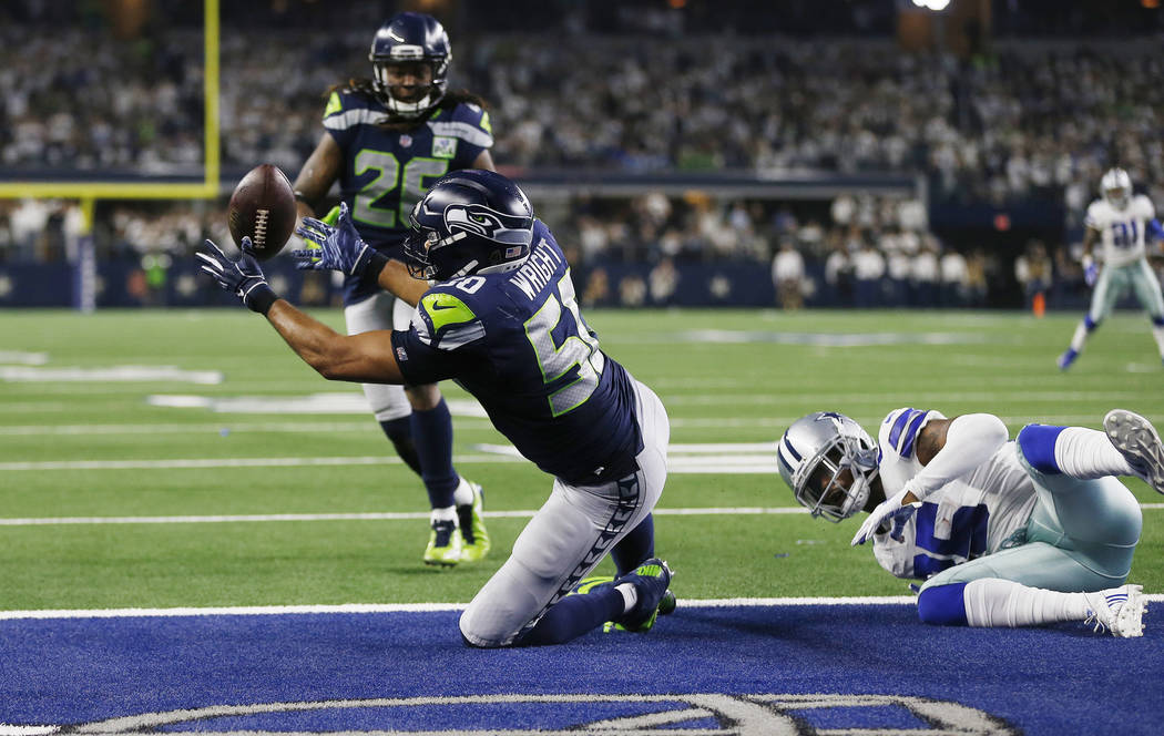 Seattle Seahawks outside linebacker K.J. Wright (50) intercepts the ball against Dallas Cowboys wide receiver Noah Brown (85) during the second half of the NFC wild-card NFL football game in Arlin ...
