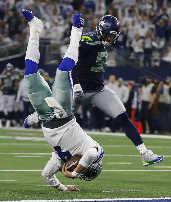 Dallas Cowboys quarterback Dak Prescott (4) flies for the goal line and makes a first down against Seattle Seahawks defensive end Frank Clark (55) during the second half of the NFC wild-card NFL f ...