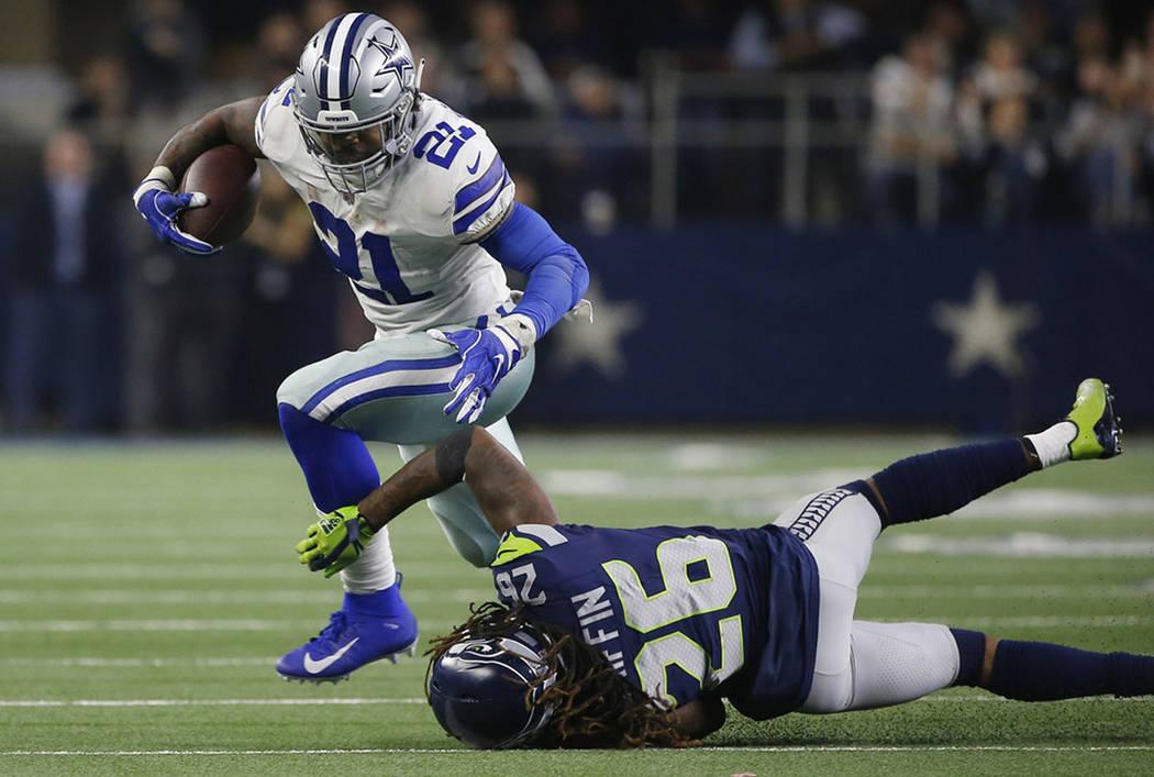 Dallas Cowboys running back Ezekiel Elliott (21) runs near Seattle Seahawks cornerback Shaquill Griffin (26) during the second half of the NFC wild-card NFL football game in Arlington, Texas, Satu ...