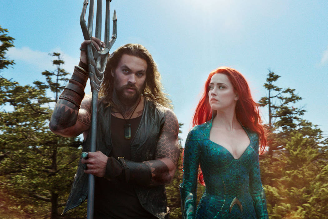 """This image released by Warner Bros. Pictures shows Jason Momoa, left, and Amber Heard in a scene from """"Aquaman."""" (Warner Bros. Pictures via AP)"""