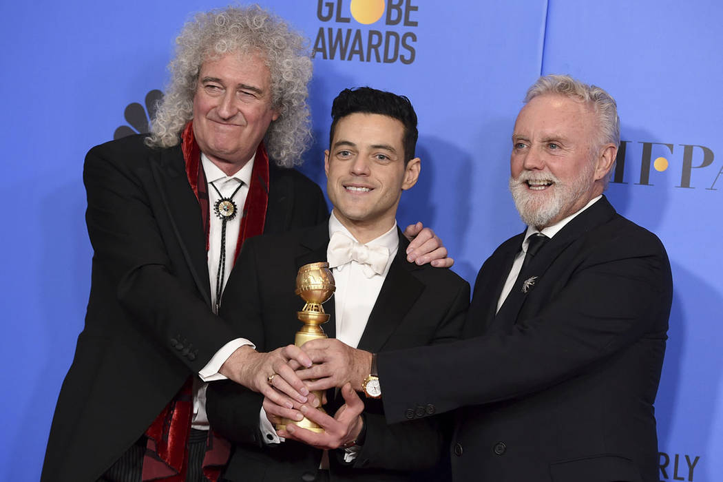 "Brian May, left, and Roger Taylor, right, of Queen, and Rami Malek pose in the press room with the award for best motion picture, drama for ""Bohemian Rhapsody"" at the 76th annual Golden ..."
