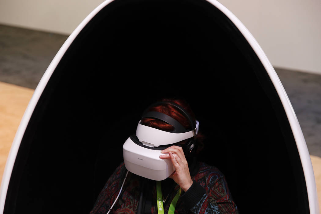 In this Jan. 9, 2018, file photo a woman wears Huawei VR2 goggles at the Huawei booth during CES International in Las Vegas. The CES 2019 gadget show, which kicks off Sunday, will showcase the exp ...