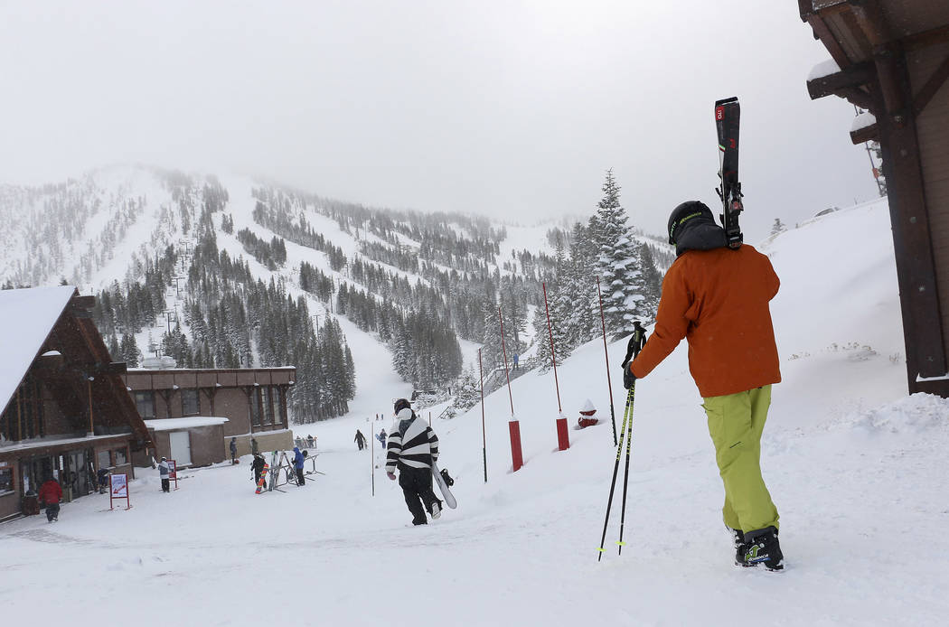 FILE - In this Nov. 29, 2018, file photo, skiers and snowboarders walk to the lifts at Mt. Rose Ski Tahoe near Reno, Nev. Avalanche warnings have been posted in parts of California, Nevada and Uta ...