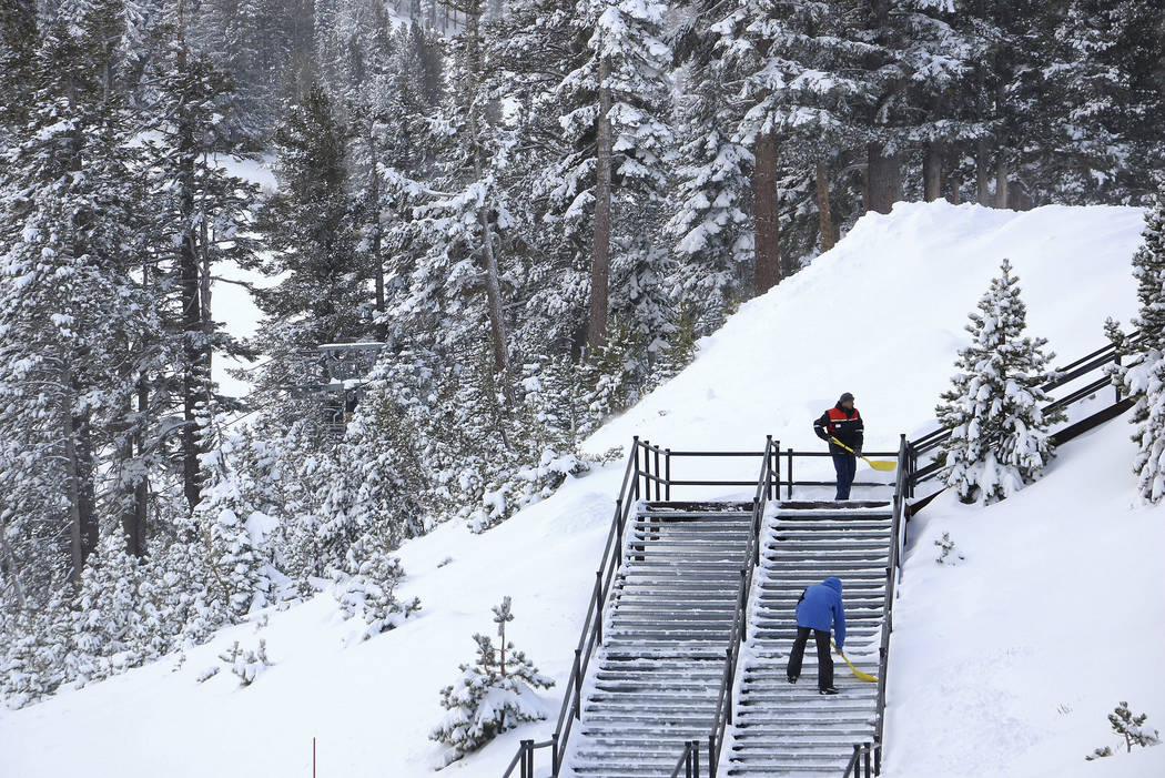 FILE - In this Nov. 29, 2018, file photo, workers shovel snow off a staircase at Mt. Rose Ski Tahoe near Reno, Nev. Avalanche warnings have been posted in parts of California, Nevada and Utah afte ...