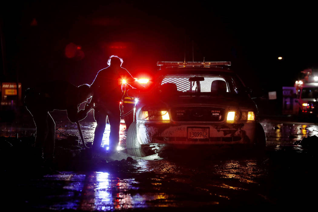 In this Saturday, Jan 5, 2019, photo sheriff's deputies work to free their patrol cruiser from mud covering a stretch of Pacific Coast Highway in Malibu, Calif. A winter storm unleashed mudslides ...