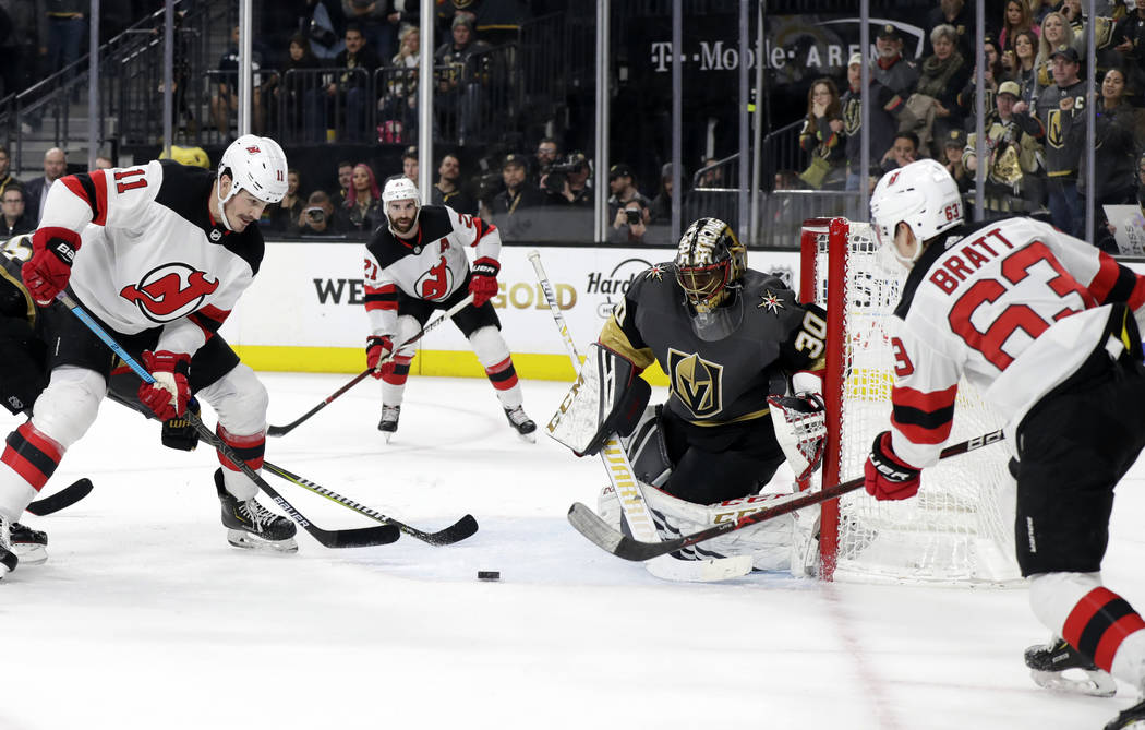 Vegas Golden Knights goalie Malcolm Subban (30) defends as New Jersey Devils left wing Jesper Bratt (63) passes to center Brian Boyle (11) during the third period of an NHL hockey game Sunday, Jan ...