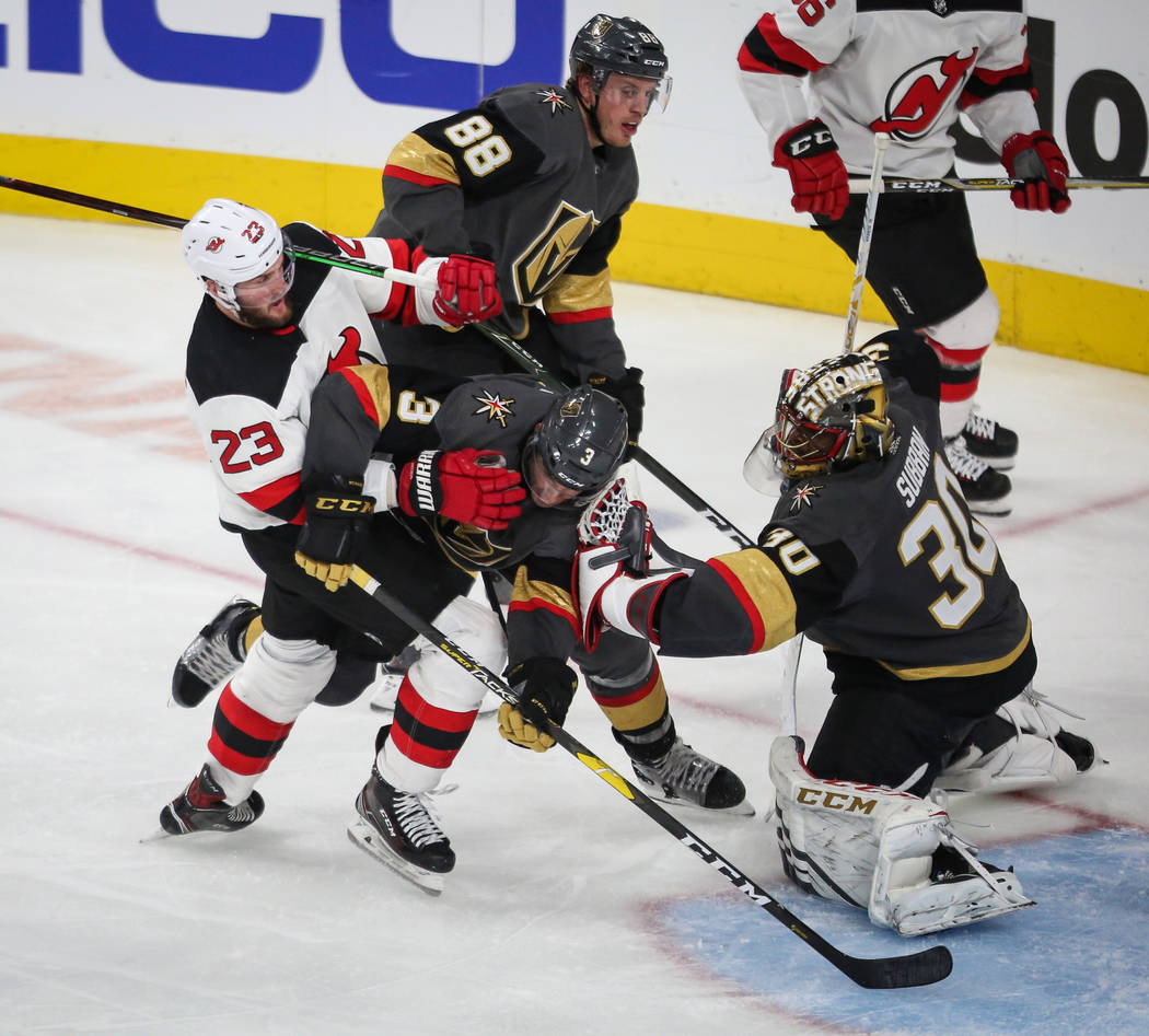 New Jersey Devils right wing Stefan Noesen (23) and Vegas Golden Knights defenseman Brayden McNabb (3) collide in front of Vegas Golden Knights goaltender Malcolm Subban (30) during the third peri ...