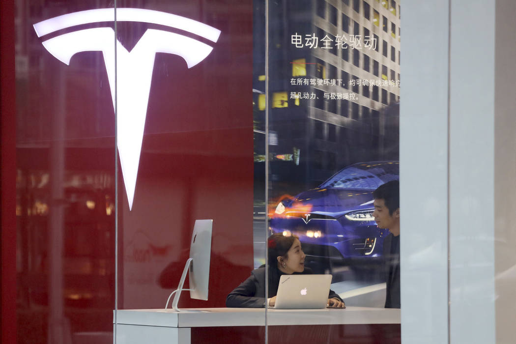 Workers chat in a Tesla store in Beijing, China, Monday, Jan. 7, 2019. Tesla Motors CEO Elon Musk said Monday on Twitter that the automaker is breaking ground for a Shanghai factory and will start ...