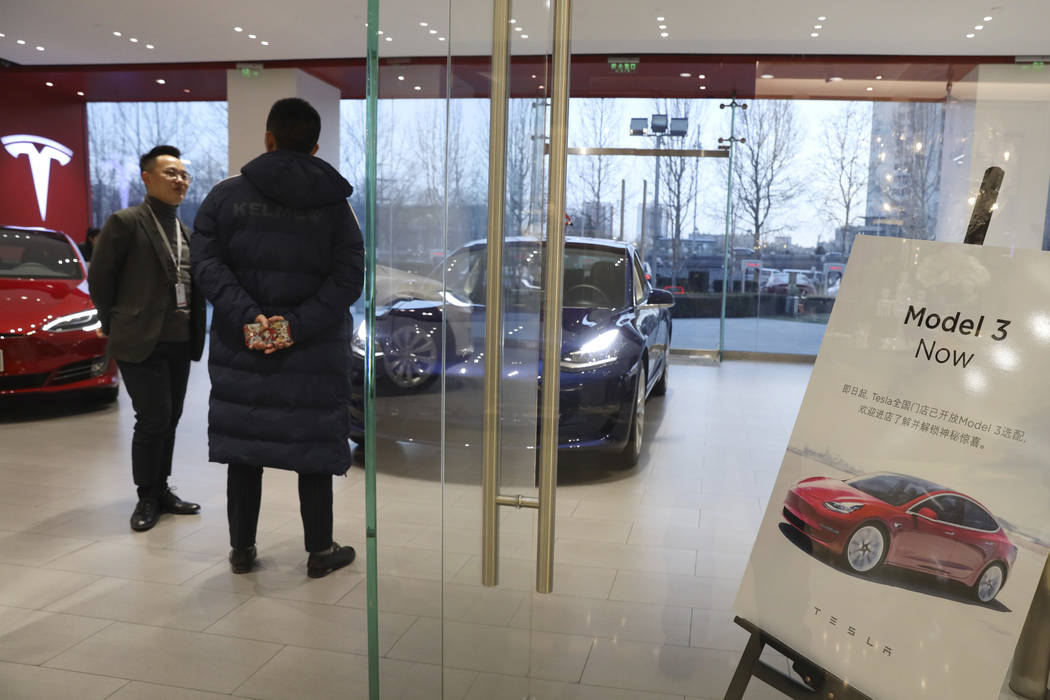A sales staff chats with a customer at a Tesla store near a poster announcing orders of the Model 3 electric cars in Beijing, China, Monday, Jan. 7, 2019. Tesla Motors CEO Elon Musk said Monday on ...