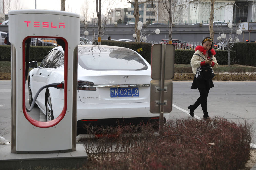 A woman walks past a Tesla car being charged in Beijing, China, Monday, Jan. 7, 2019. Tesla Motors CEO Elon Musk said Monday on Twitter that the automaker is breaking ground for a Shanghai factory ...