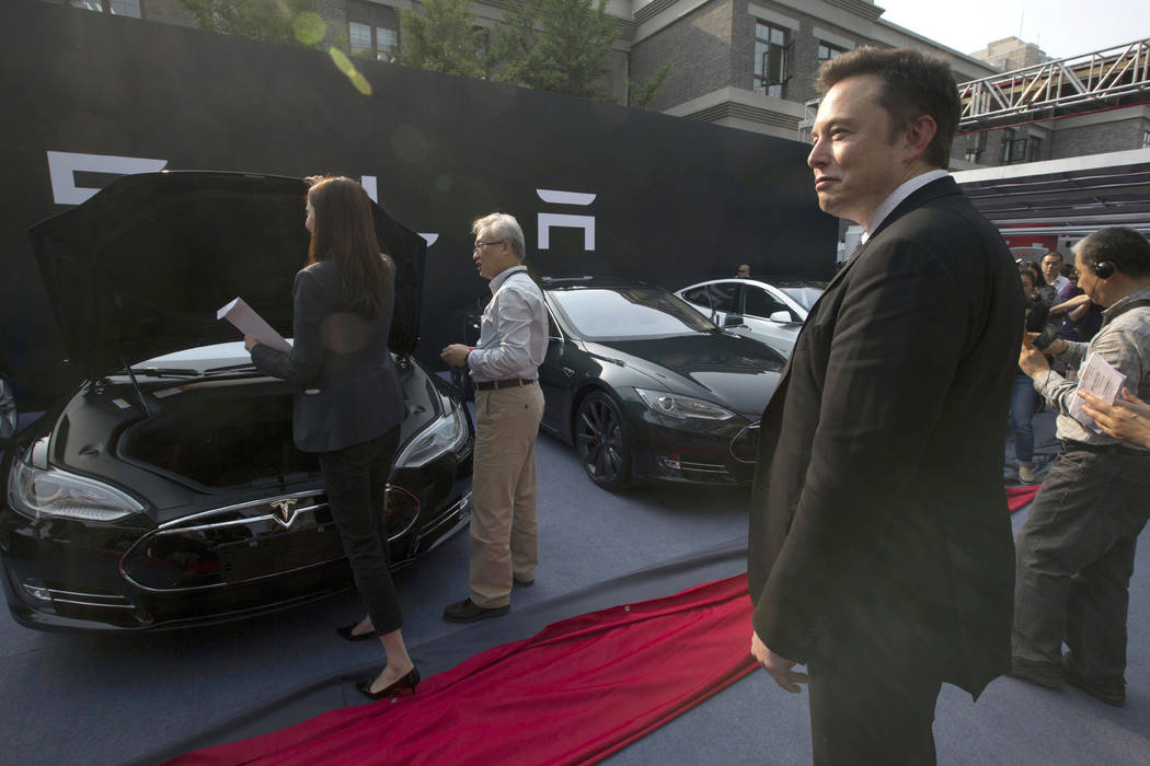 Tesla Motors CEO Elon Musk, right, looks on as a set of Tesla Model S sedans are delivered to its first customers in China at an event in Beijing, April 22, 2014. Musk said Monday, Jan. 7, 2019 on ...