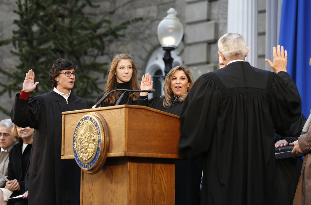 Nevada Supreme Court Justices, Lidia Siglich, left, Abbi Silver, center, and Elissa Cadish, not seen, take the oath of office with Supreme Court Chief Justice James Hardesty during the inaugurati ...