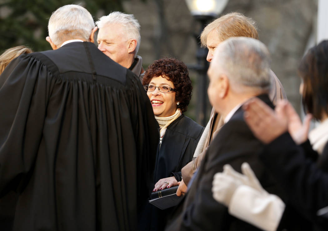 Nevada Supreme Court Chief Justice James Hardesty congratulates Justice Elissa Cadish, center, after she is sworn in during the inauguration at the Capitol, in Carson City, Nev., on Monday, Jan. 7 ...