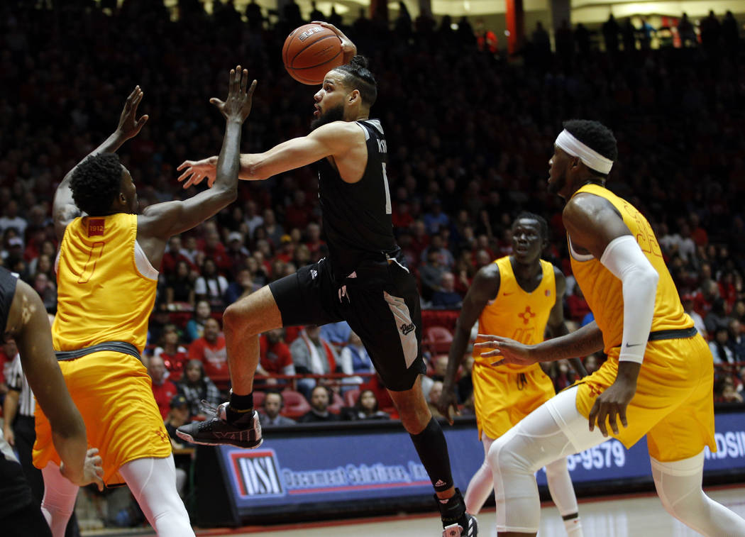 UNR forward Caleb Martin drives to the basket as he's defended by New Mexico forward Corey Manigault, left, during the first half of an NCAA college basketball game in Albuquerque, N.M., Saturday, ...