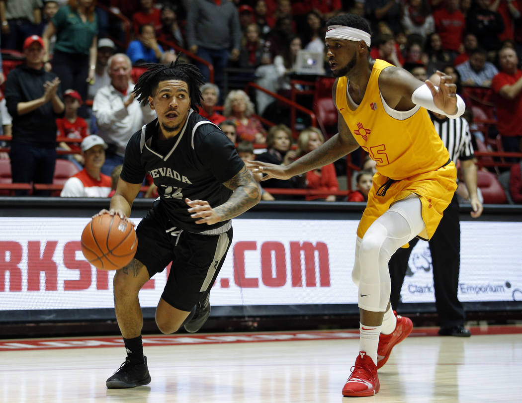 UNR guard Jazz Johnson, left, dribbles to the basket escorted by New Mexico forward Carlton Bragg during the first half of an NCAA college basketball game in Albuquerque, N.M., Saturday, Jan. 5, 2 ...
