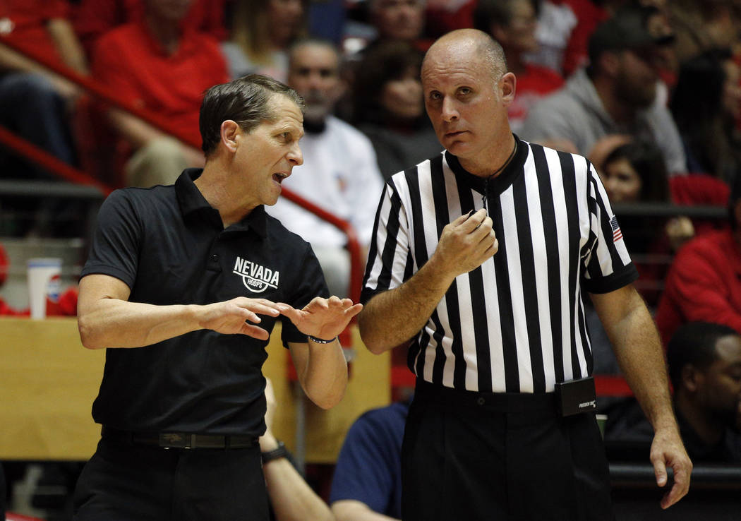 UNR head coach Eric Musselman, left, speaks with official Michael Greenstein during the second half of an NCAA college basketball game against New Mexico in Albuquerque, N.M., Saturday, Jan. 5, 20 ...