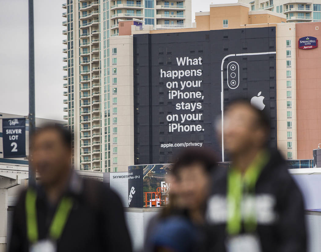 Visitors walk past an Apple advertisement on the south side of SpringHill Suites that is easily visible from the CES 2019 tech show at the Las Vegas Convention Center on Monday, Jan. 7, 2019, in L ...