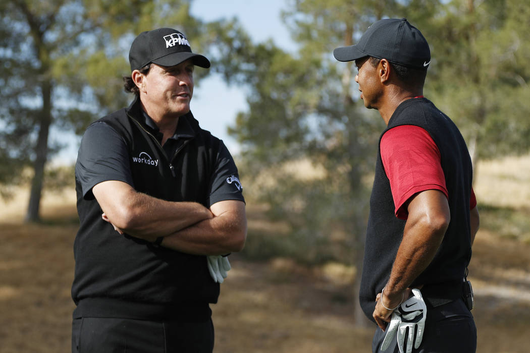 Phil Mickelson, left, and Tiger Woods talk at the first tee before a golf match at Shadow Creek golf course, Friday, Nov. 23, 2018, in Las Vegas. (AP Photo/John Locher)