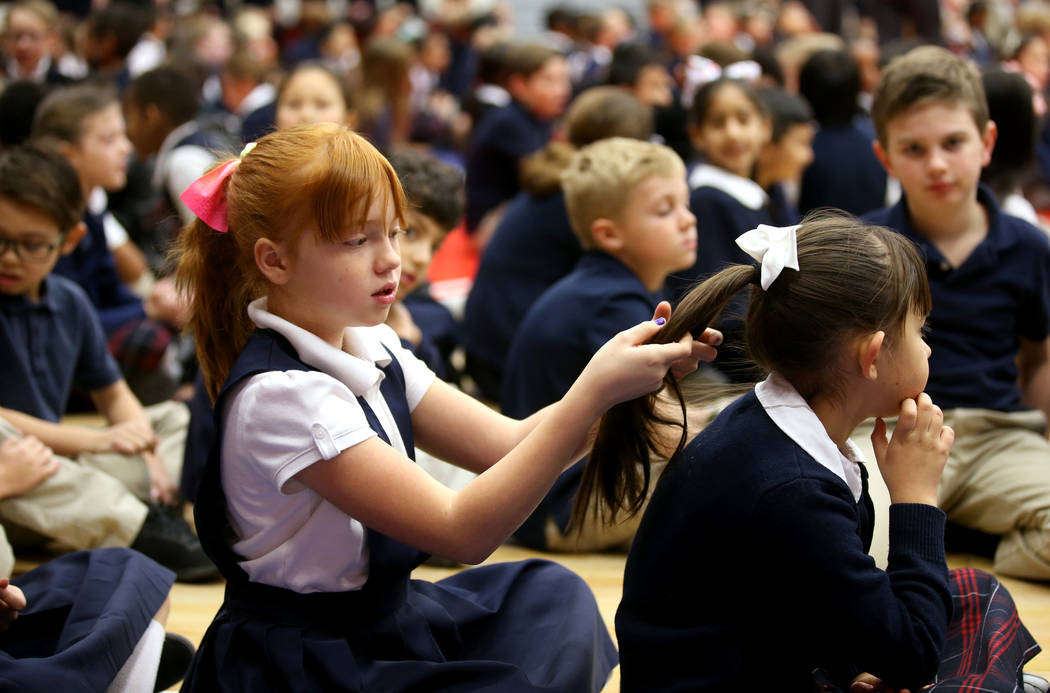 Students including third graders Karli Atkinson, left, and Mia Nielsen gather for an assembly in the gym at American Preparatory Academy charter school in Las Vegas Thursday, Jan. 3, 2019. K.M. Ca ...