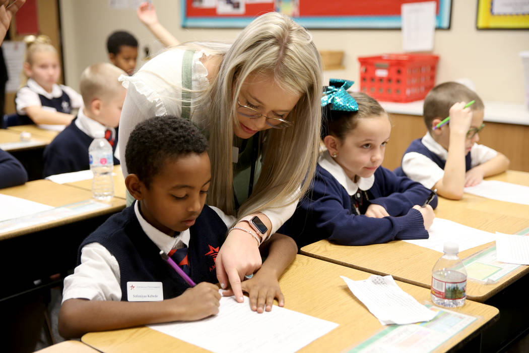 Instructor Meriah Jex helps Sofoniyas Kebede, left, and Madelyn Morris in Kaylie Gunn's fourth grade class at American Preparatory Academy charter school in Las Vegas Thursday, Jan. 3, 2019. K.M. ...