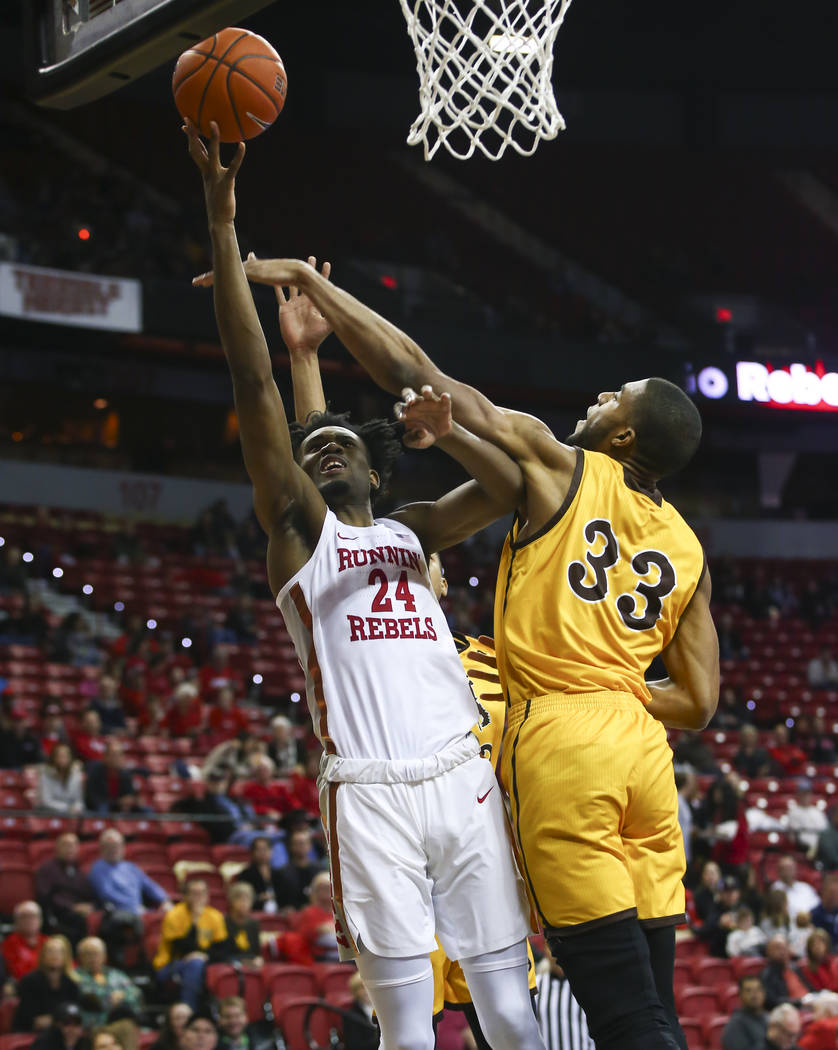 UNLV Rebels forward Joel Ntambwe (24) is fouled by Wyoming Cowboys forward Jordan Naughton (33) while going to the basket during the first half of a basketball game at the Thomas & Mack Center in ...