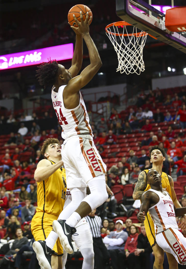 UNLV Rebels forward Joel Ntambwe (24) goes to the basket on an alley-oop pass from UNLV Rebels guard Amauri Hardy, bottomr right, during the second half of a basketball game against Wyoming at the ...
