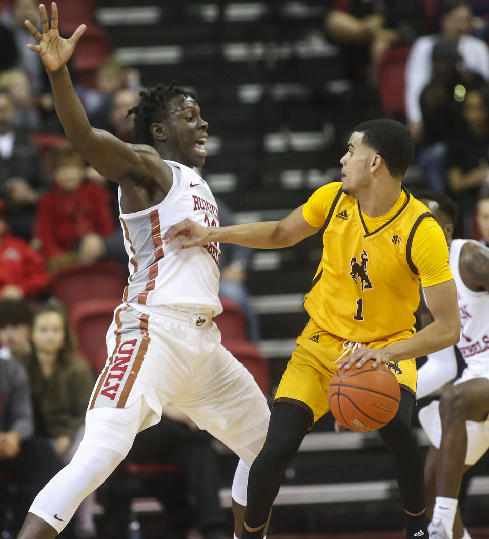 UNLV Rebels forward Joel Ntambwe (24) defends as Wyoming Cowboys guard Justin James (1) moves the ball during the second half of a basketball game at the Thomas & Mack Center in Las Vegas on S ...