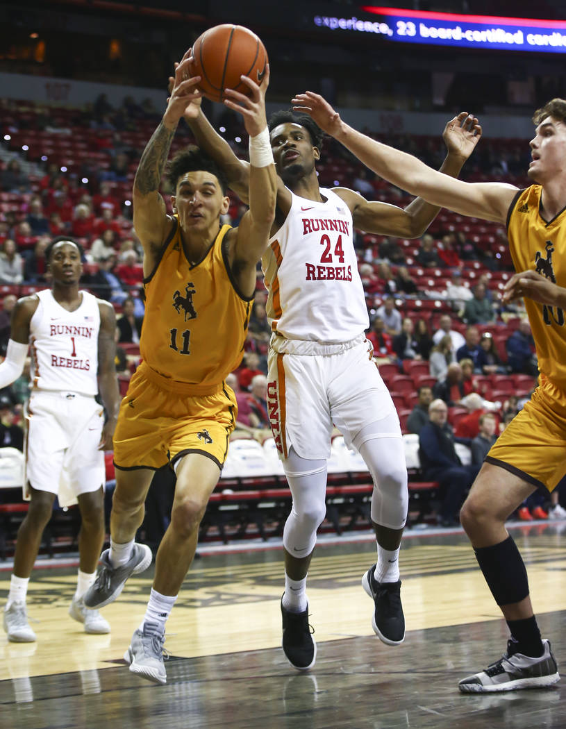 Wyoming Cowboys forward Trace Young (11) gets a rebound against UNLV Rebels forward Joel Ntambwe (24) during the first half of a basketball game at the Thomas & Mack Center in Las Vegas on Sat ...