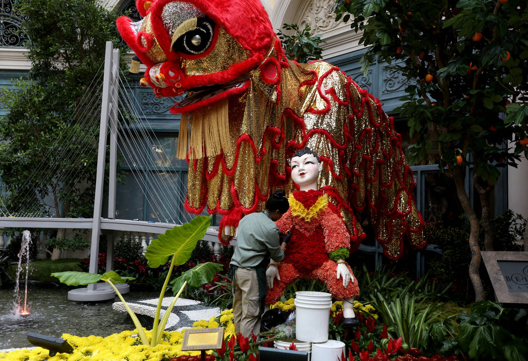 A work places flowers into a statue of a child at the Chinese New Year Year of the Pig display at the Bellagio Conservatory at the Bellagio in Las Vegas, Monday, Jan. 14, 2019. Rachel Aston Las Ve ...