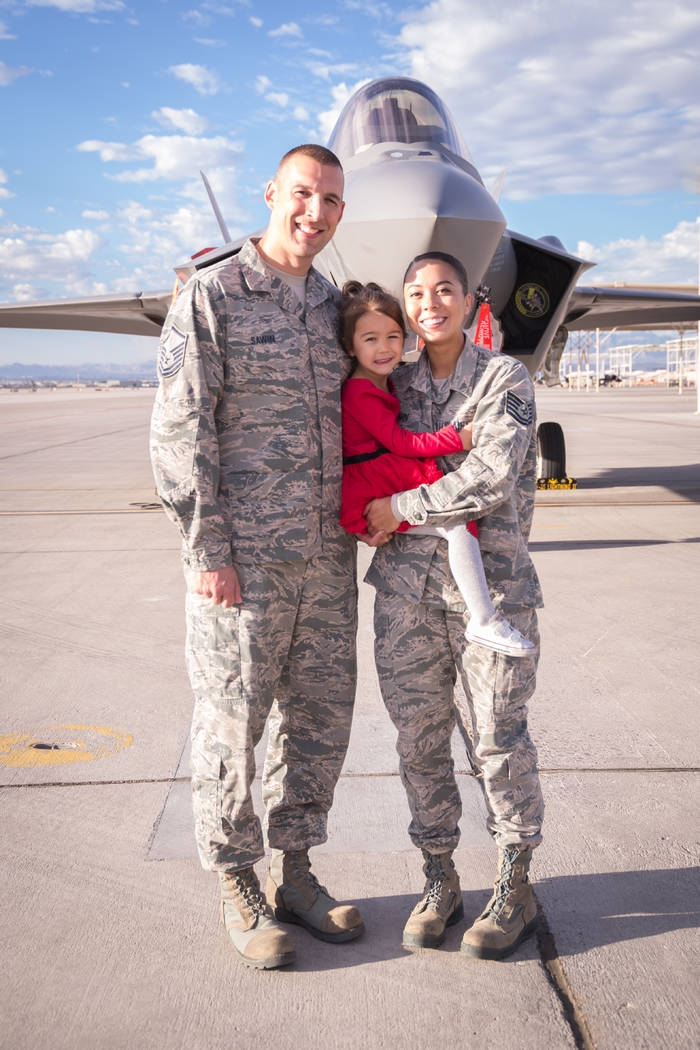 Alexandria Sawin and her husband, Phil, pose with their daughter, Isabelle, in front of the F-35 Lightning fighter aircraft that she worked on while in the Reserves. (Alexandria Sawin).