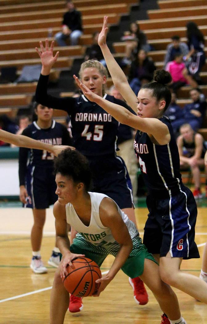 Green Valley High School's Rian Anderson (12) tries to pass through Coronado High School's Haley Morton (45) and Gabriela Etopio (15) at Green Valley High School in Henderson, Monday, Jan. 7, 2019 ...