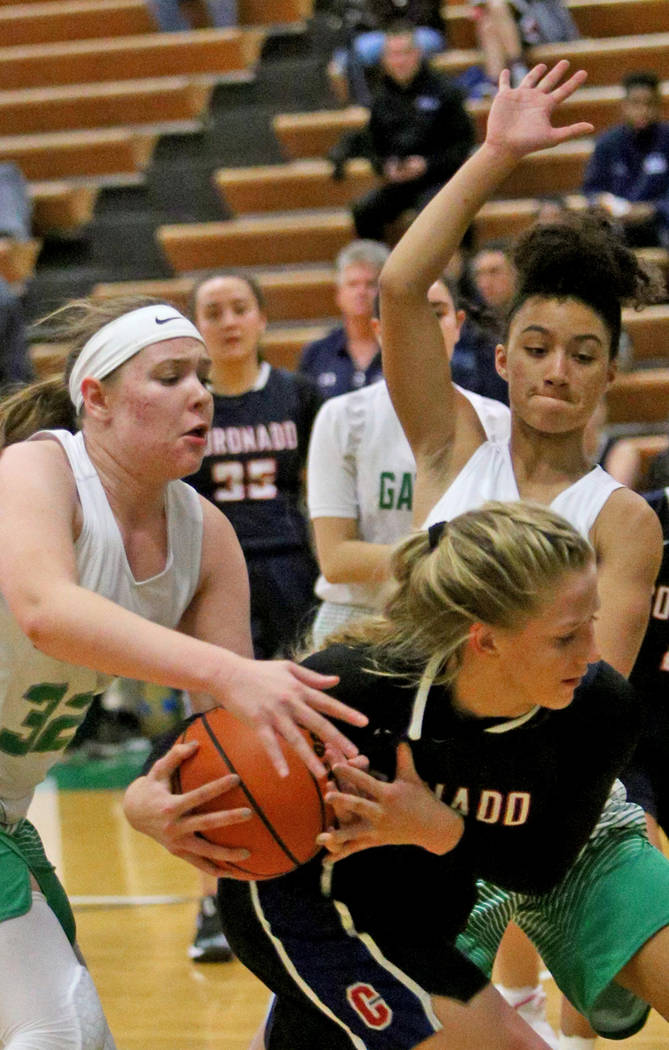 Coronado High School's Haley Morton (45) tries to pass the ball through Green Valley High School's Angelia Frenzel (32) and Rain Anderson (12) at Green Valley High School in Henderson, Monday, Jan ...
