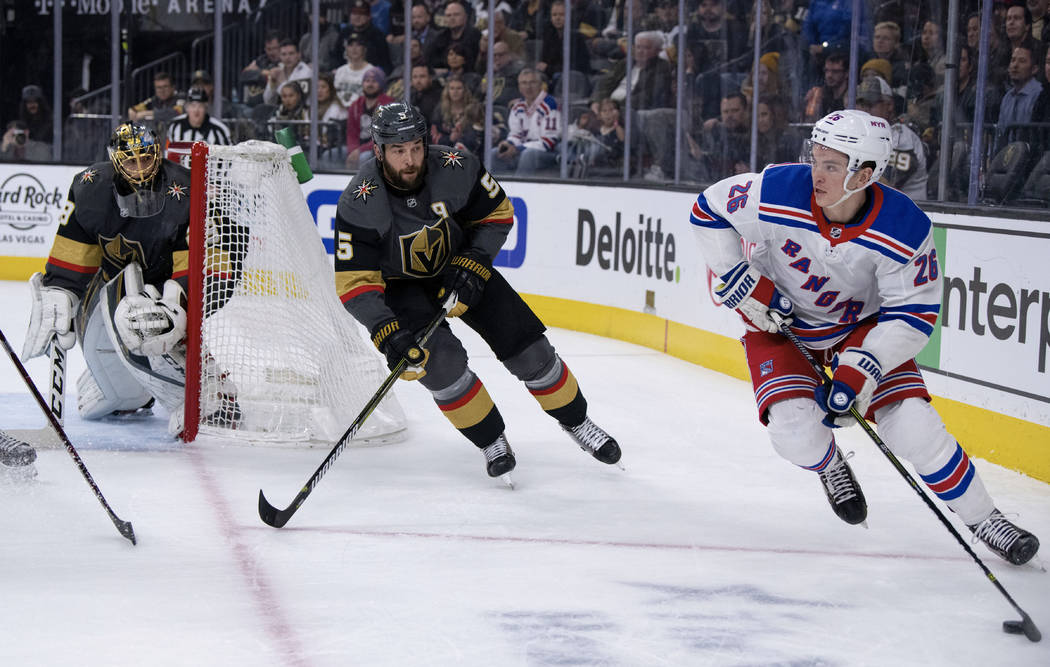 New York Rangers left wing Jimmy Vesey looks for a pass while being defended by Vegas Golden Knights defenseman Deryk Engelland during the first period of an NHL hockey game Tuesday, Jan. 8, 2019, ...