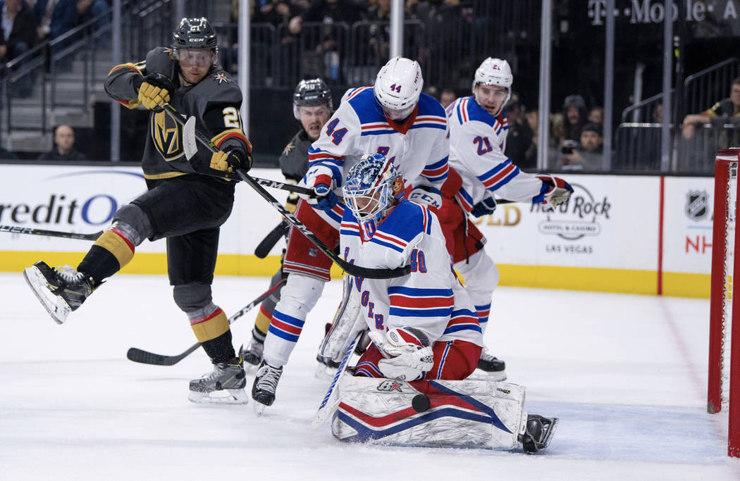 Vegas Golden Knights center Cody Eakin and New York Rangers defenseman Neal Pionk and goalie Alexandar Georgiev vie for the puck during the second period of an NHL hockey game Tuesday, Jan. 8, 201 ...