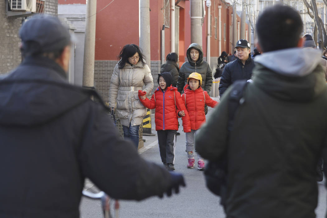 Children are escorted from the site of an attack at the Beijing No. 1 Affiliated Elementary School of Xuanwu Normal School in Beijing, China, Tuesday, Jan. 8, 2019. A male attacker injured 20 chi ...