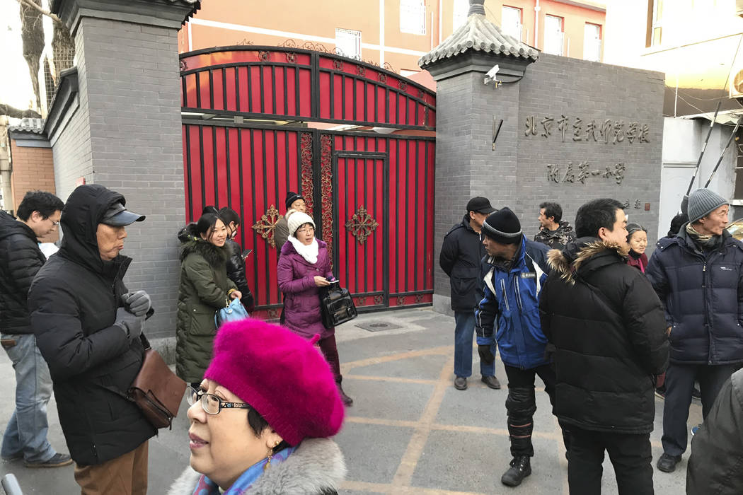 Parents gather at an entrance gate to the Beijing No. 1 Affiliated Elementary School of Xuanwu Normal School following an attack in Beijing, China, Tuesday, Jan. 8, 2019. A male attacker injured 2 ...
