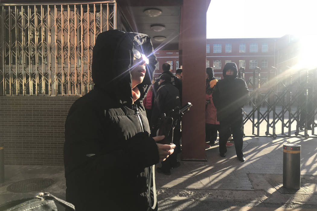 Parents wait outside the entrance to the Beijing No. 1 Affiliated Elementary School of Xuanwu Normal School in Beijing, China, Tuesday, Jan. 8, 2019. A male attacker injured 20 children Tuesday in ...