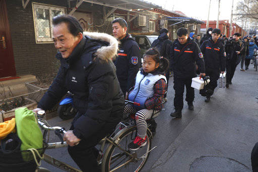 A man rides with a student pass crime scene investigators as they leave the Beijing No. 1 Affiliated Elementary School of Xuanwu Normal School in Beijing, China, Tuesday, Jan. 8, 2019. A male atta ...