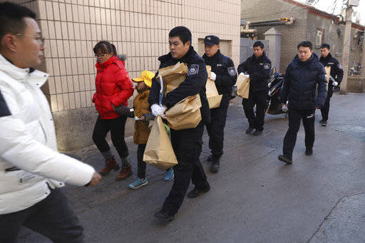 A woman walks away with a child as they leave the Beijing No. 1 Affiliated Elementary School of Xuanwu Normal School near crime scene investigators as they carrying evidence bags in Beijing, China ...