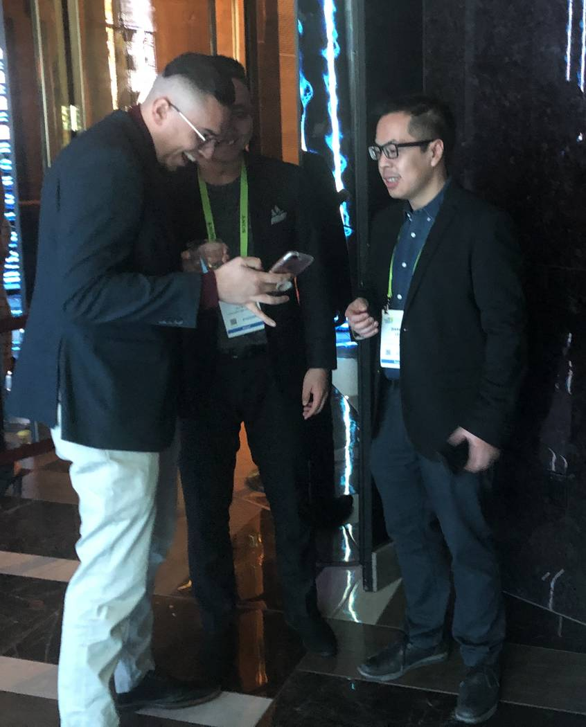 Conventioneers Rinzi Sheka, left, and Darryl Lee of Calgary look over photos they took durin the CES 2019 C Space Party presented by Jewel Nightclub at Aria in Las Vegas Monday, Jan. 7, 2019. John ...